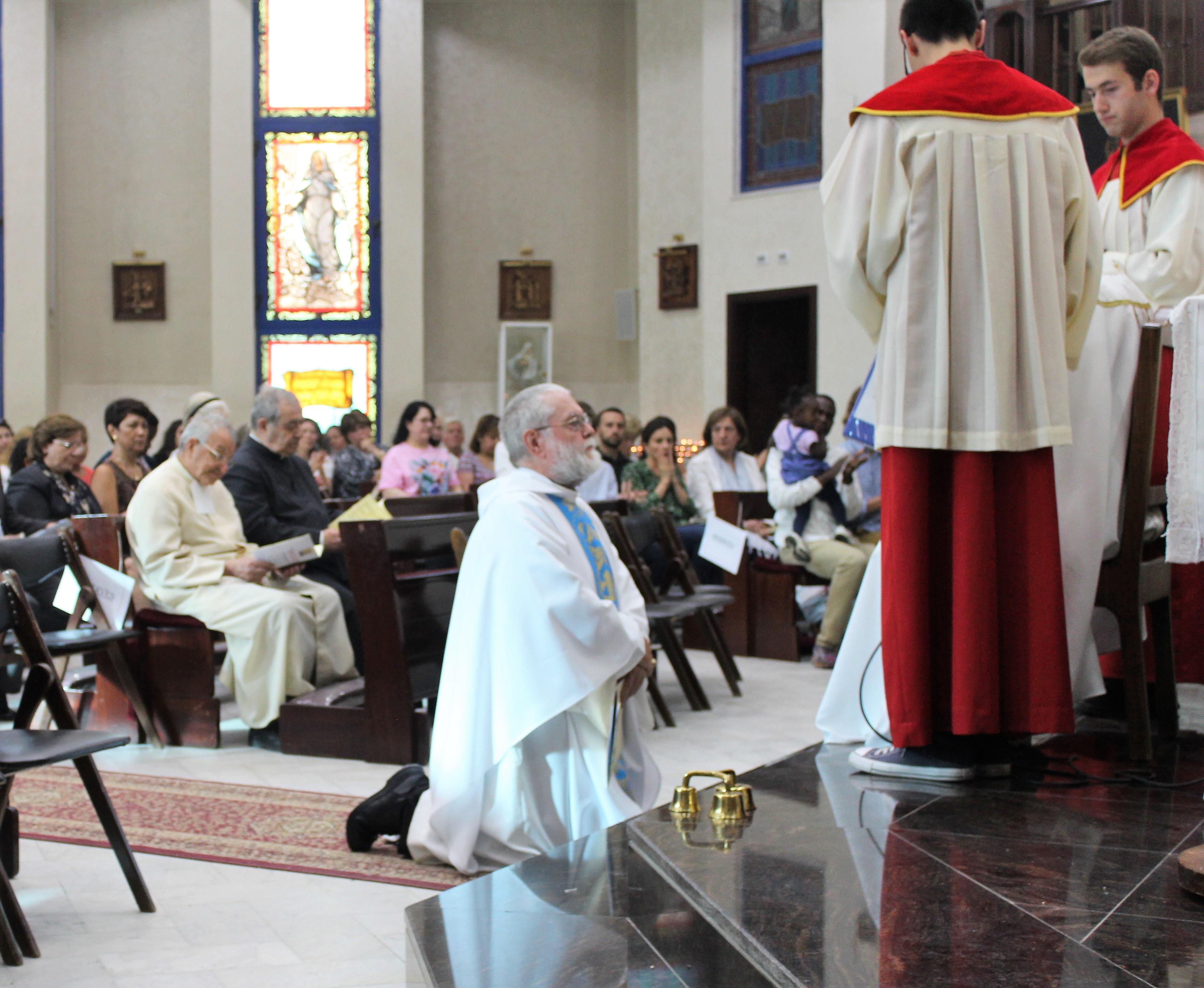 Fr. John kneeling before the Bishop
